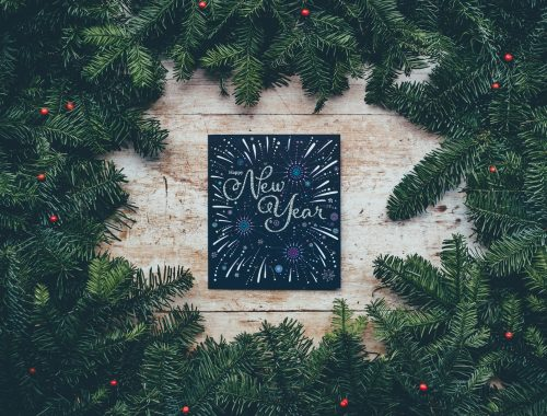 New Year card surrounded by greenery