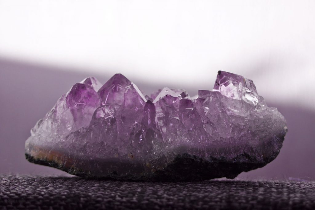Amethyst stone on grey background